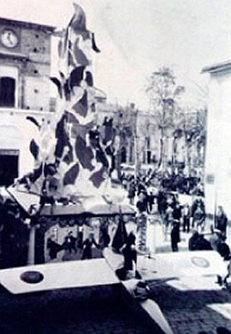 """En 1982 se va """"plantar"""" la primera falla en el nucli antic de la ciutat de Sagunt. La comissió fallera va tindre els seus origens, un any abans, en la Societat Viti-vinícola Saguntina. Un avió simbolizava l'arribada del nou regim republicá. Unes columnas simbolizaven l'economia, el treball, la música, etc. Els ninos al-lusius al treball van ser indultats i regalats a l'alcalde de la ciutat, Joan Chabert i Bru."""
