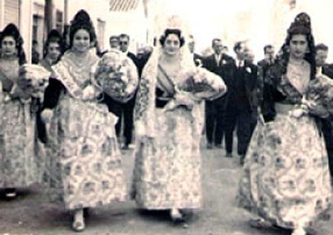 Setmana fallera. Era en els anys 50 del segle XX. Un grup de fallers de Port de Sagunt portant rams de flors desfila seguides per la comissió.